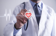Doctor With Stethoscope Holding Red Heart With Cardiogram.