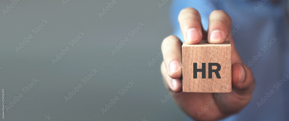 Fototapeta Man holding HR word on wooden cube.
