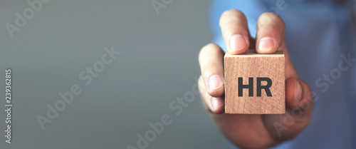 Man holding HR word on wooden cube. Fotobehang