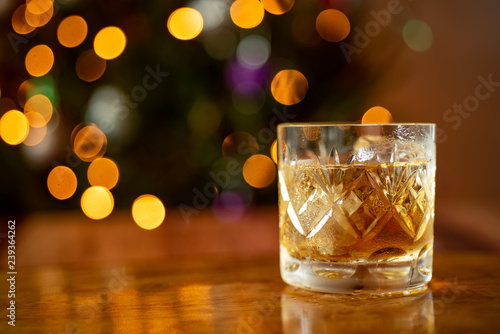 Glass of whiskey bourbon in a crystal glass up close shot Christmas lights backg Canvas Print