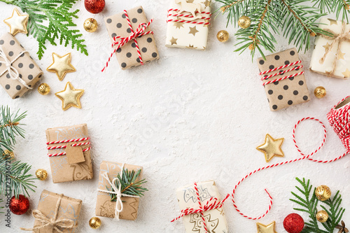Fototapeta Decorated Christmas gift boxes, gold ornaments, bakers twine & spruce frame on white background. Cristmas preparation. Copy space. obraz