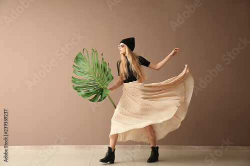 Beautiful woman with green tropical leaf near color wall