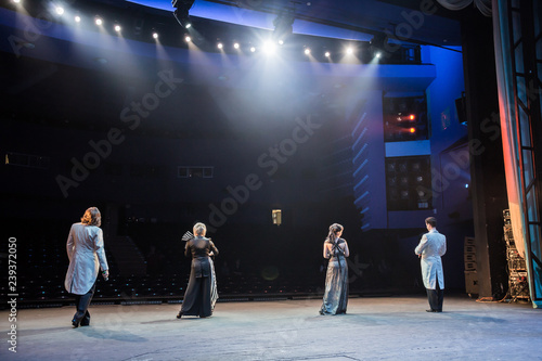 Actors on stage during a performance or rehearsal in the theater. The stage of the theatre or the Opera, with lighting equipment. Light and spotlight on the stage. - 239372050