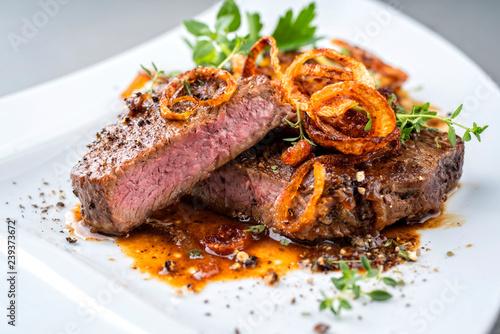Keuken foto achterwand Steakhouse Klassischer Zwiebelrostbraten serviert mit Röstzwiebel und Kräuter als closeup auf einem Modern Design Teller
