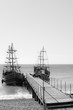 Two wooden sailing ships at the wooden pier.