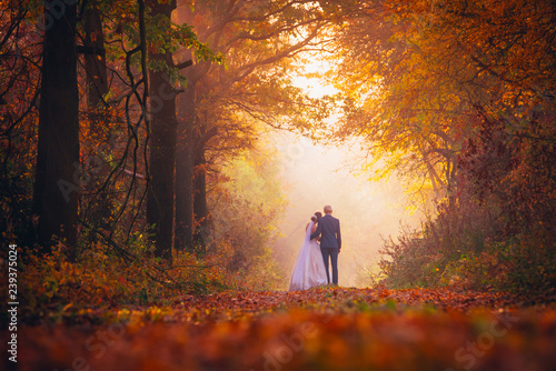 Photo sur Aluminium Arbre Bride and groom in colorful autumn forest