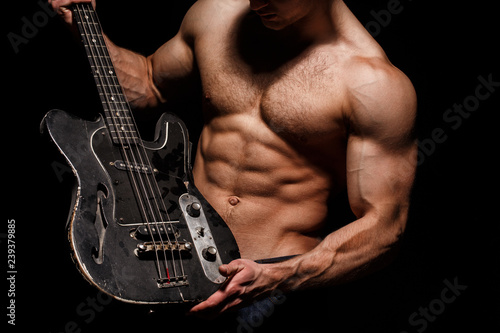 Fototapety, obrazy: Guitar. Torso man. Play the guitar. Chest muscles, Six pack, ab, triceps. Music festival. Instrument on stage and band. Strong, muscular, muscles man, bodybuilding. Music concept. Electric guitar.