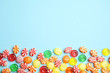Leinwanddruck Bild - Flat lay composition with delicious colorful candies and space for text on color background