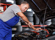 Technician working at service station, repairing car