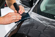 Car wrapping specialist putting vinyl foil or film on car. Protective film on car. Applying a protective film to the car with tools. Car detailing. Transparent film. Car paint protection. Trimming.