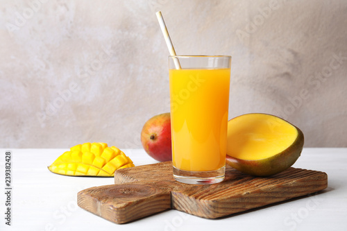 Glass with fresh mango juice and tasty fruits on table. Space for text