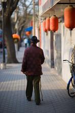 Senior Man Walking With A Cane Down An Urban Street.