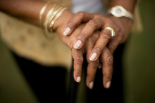 Mature Woman's Hands Adorned With Gold Jewelry.