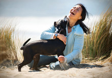 Laughing Young Woman Embracing Her Dog On A Beach.