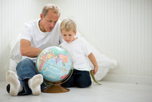 Mid-adult Man Sitting With His Young Son Looking At A Globe.