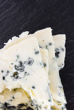 Cheese With Mold On A Board Of Stone. Sliced Gorgonzola Cheese Close-up On The Surface Of Slate.