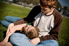 Teenage Girl Lying With Her Head In Her Boyfriends Lap And Looking Up At Him On A Grassy Field.
