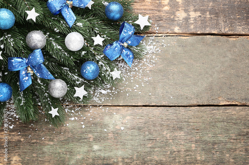 Foto  Christmas fir tree branches with decorations on grey wooden table