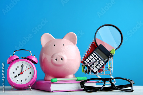 Fotografía  Pink piggy bank with alarm clock and school supplies on wooden table