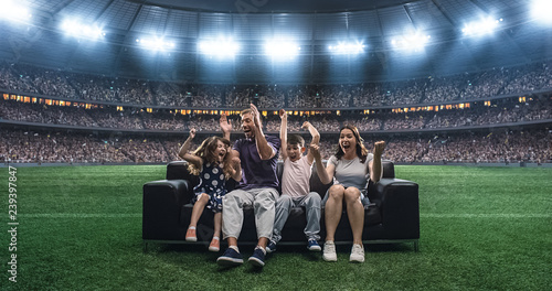 Fotografía  A family is watching a soccer moment, sitting on the couch located in the middle of the soccer stadium