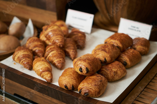 Fotografia, Obraz Plain croissant and chocolate puff pastry buns, on restaurant bu