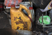 Empty Old Plastic Container/ Greasy Diesel Bottle/ Dirty Lubricant Oil Can With Peeled Label- Messy Garage With Tools And Broken Engine