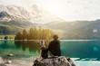 canvas print picture - Mensch umarmt Hund auf einem Felsen mit Blick auf einen wunderschönen See mit Bergen und Bäumen