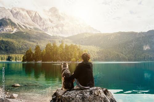 Mensch umarmt Hund auf einem Felsen mit Blick auf einen wunderschönen See mit Be Fototapete