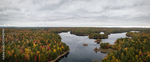 Aerial panoramir view of a beautiful lake in the forest with colorful trees during fall season. Taken in Grand Lake Flowage, Nova Scotia, Canada.