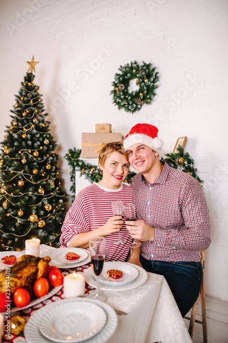 Love At The Christmas Table.Couple In Love With Santa Claus Caps At The Christmas Table