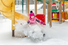 Little Cute Baby Girl Having Fun On Playground At Winter. Children Winter Sport And Leisure Outdoor Activities