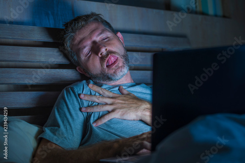 man alone in bed playing cybersex using laptop computer watching porn sex movie late at night with lascivious pervert face expression in internet pornographic sexual content - 239434259