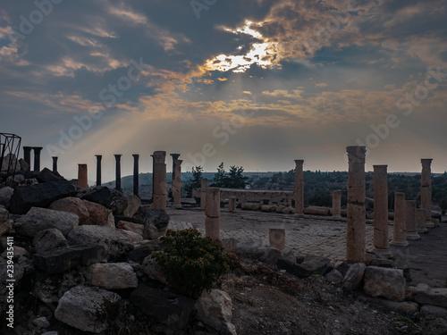 Fotografie, Obraz  Sun shinning through the clouds over Roman ruins