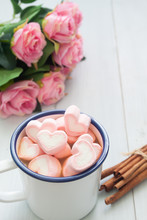 Hot Chocolate With Heart Shape Marshmallows On Top. Sweet Beverage And Pink Roses On Table
