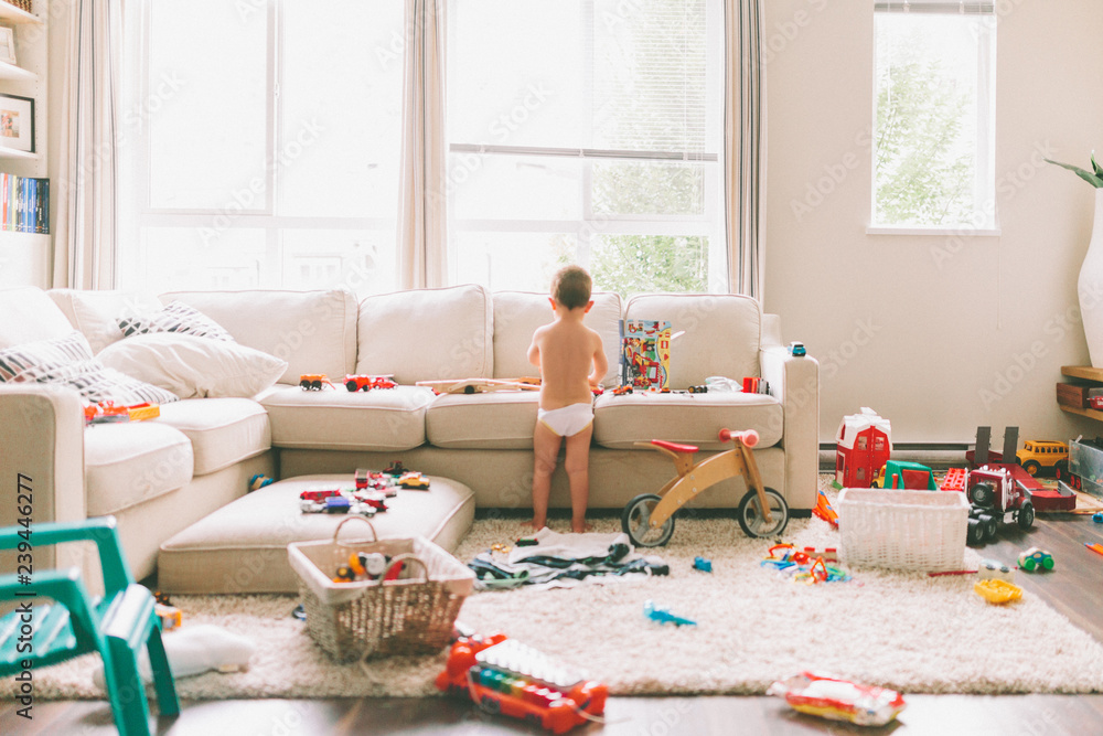 Fototapety, obrazy: A little boy playing in a messy living room.