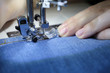 Woman working on the sewing machine, female hands close-up. Seamstress sews jeans, concept of mending clothes, textile industry