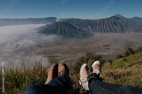 Photo  Legs of couple traveler sitting on a high mountain top in travel