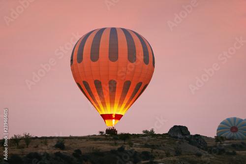 Fotografia Hot Air Balloon With Fire Light At Morning Valley In Cappadocia