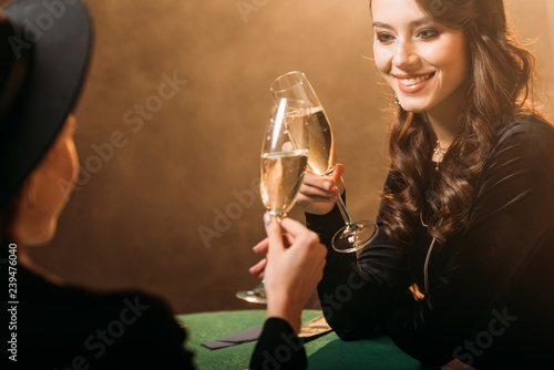 Photo  smiling attractive women clinking with glasses of champagne at poker table in ca