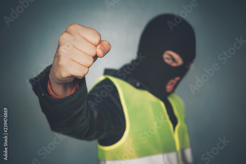Valokuva  Rebellious protester in a mask shows his fist