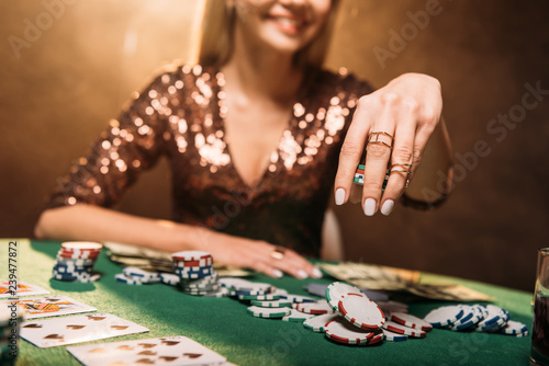 Photo  cropped image of smiling girl playing poker at table in casino