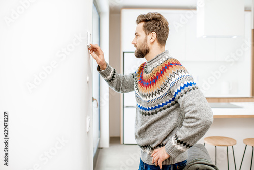 Fotografía  Man in sweater adjusting room temperature with electronic thermostat at home
