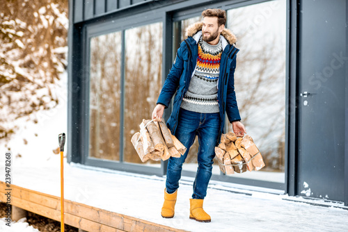 Foto Handsome man in winter clothes carrying firewoods on the terrace near the modern