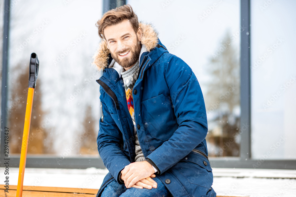 Fototapeta Portrait of a handsome man in winter clothes sitting on the terrace of the modern house