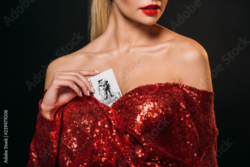 фотография  cropped image of girl in red shiny dress hiding joker card in dress isolated on