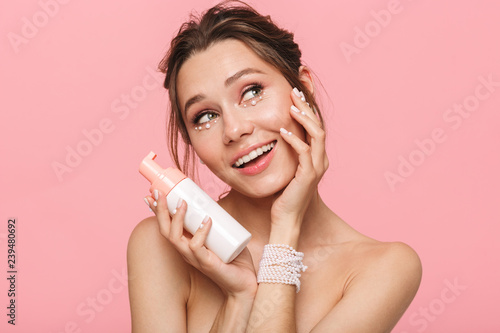 Pretty young woman posing isolated over pink wall background take care of her skin with cream Canvas Print