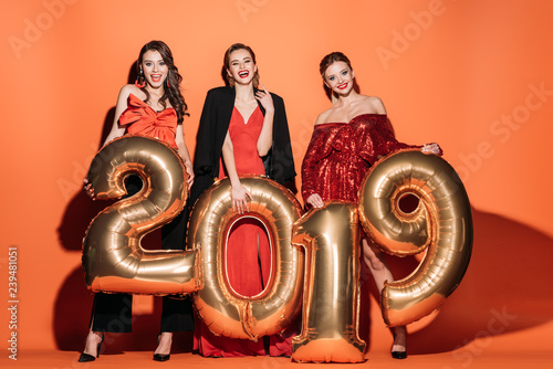 Photo  smiling attractive girls in stylish party clothes holding 2019 balloons on orang