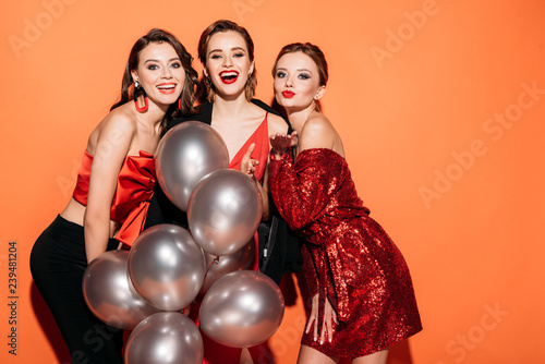 laughing beautiful girls in stylish party clothes holding bundle of grey balloon Canvas Print