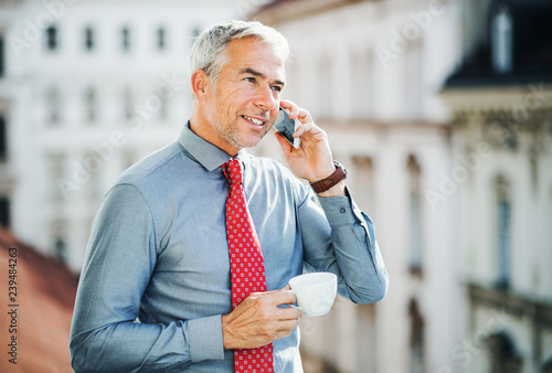 Mature businessman with smartphone standing on a terrace in city, making a phone call Wallpaper Mural