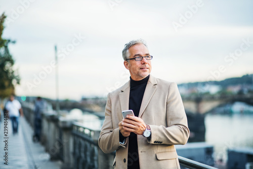 Foto  Mature businessman with smartphone standing by river in Prague city, using smartphone